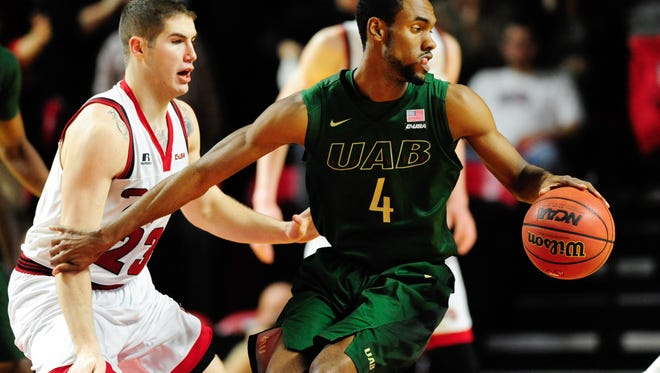 UAB guard Robert Brown (4) dribbles the ball as Western Kentucky forward Justin Johnson (23) defends during the second half at E.A. Diddle Arena. The Hilltoppers won 69-62.