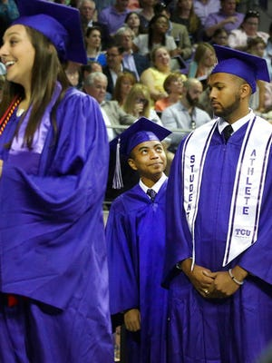 Fourteen year old Carson Huey-You looks up at fellow graduate Adam Christopher Hood as they prepare to receive their diplomas on stage at the Texas Christian University commencement held in Fort Worth, Texas, on Saturday, May 13, 2017. Huey-You, the youngest student ever to attend Texas Christian University, also double minored in math and Chinese since enrolling in 2013. (Louis DeLuca /The Dallas Morning News via AP)