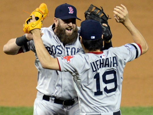 Red Sox relief pitcher Koji Uehara celebrates with first baseman Mike Napoli after defeating the Cardinals at Busch Stadium.