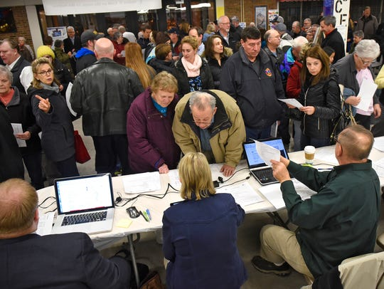 Caucus goers check in at a table near an entrance to Apollo High School during the Senate District 14 Republican Caucus in St. Cloud in this 2016 file photo.