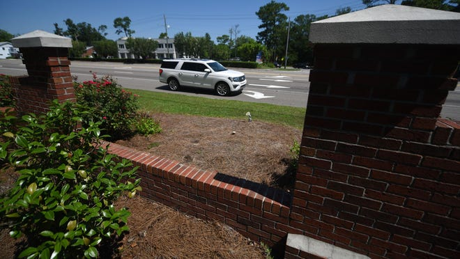 Cars on Oleander Drive drive by signs for Hugh MacRae Park that have been removed in Wilmington, N.C., Tuesday, July 14, 2020. The New Hanover Board of Commissioners voted Monday to change the name of county-owned park to Long Leaf Park.