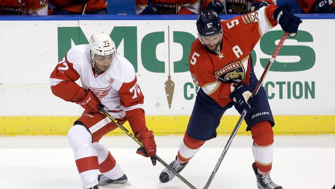 Red Wings center Andreas Athanasiou and Panthers defenseman Aaron Ekblad battle for the puck during the first period Saturday in Sunrise, Fla.
