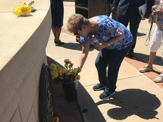 Elaine Simmons bend to take a yellow rose, which she placed at the base of the seal of one of the branches of the armed forces Monday at the annual Memorial Day ceremony at Texas State Veteran Cemetery at Abilene.
