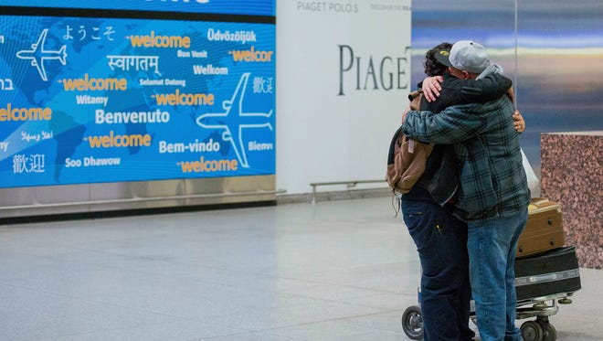 Abdullah Alghazali, right, hugs his son, Ali, in February after the Yemeni boy arrived at Kennedy Airport in New York City.