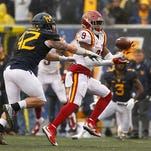 Quenton Bundrage of the Iowa State Cyclones drops a pass against Jared Barber of the West Virginia Mountaineers during the game on November 28, 2015 at Mountaineer Field in Morgantown, West Virginia.
