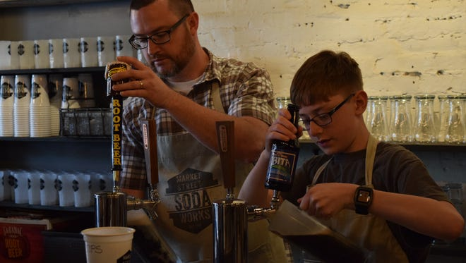Father and son Tim and Parker Argyle pour drafts during the grand opening of the Market Street Soda Shop Friday.