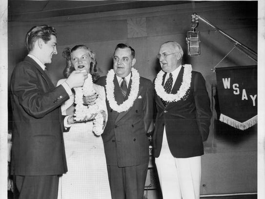 """loral wreaths flown in from Honolulu are shown being presented by WSAY Program Director George LiButti (from left) to Jean Seelbach, U of R May Queen, Vice Mayor Frank Van Lare and Frank E. Gannett during a radio """"salute"""" from KHOM, Hawaii. (This archive photo is undated.)"""