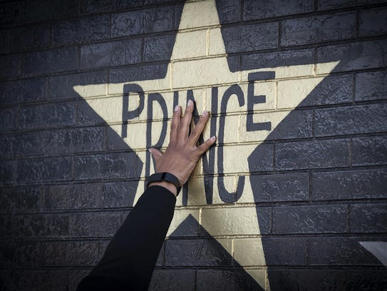 A fan touches the Prince star on the exterior of the