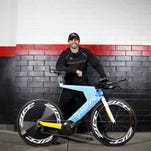 Ruster Sports founder and CEO T.J. Tollakson stands with his 2014 Dimond superbike for triathletes. The high-end ride is manufactured in the company's production facility in Des Moines.