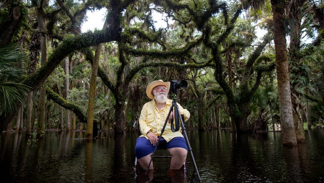 Iconic landscape photographer Clyde Butcher poses for a portrait in Myakka River State Park in Sarasota, Fla., on Thursday, Aug. 3, 2017. This was his seventh attempt to take this image at this location, and he finally captured it. Butcher is recovering from a stroke he had in May, so instead of using his large format film camera, he is using a smaller digital camera and a walker with a seat to help him get around.