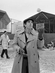FILE - In this Jan. 20, 1982, file photo, CBS Sportscaster Brent Musburger plays with a snowball outside the Silverdome in Pontiac, Mich., where the XVI Super Bowl was played.