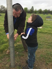 Dennis Nottingham and Henry, 4, adjust the flag at