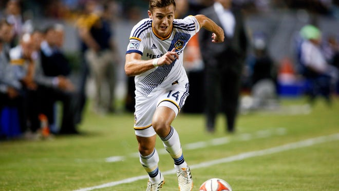 In this Aug. 27, 2014, file photo, Los Angeles Galaxy's Robbie Rogers, the first openly gay player in MLS, controls the ball against D.C. United during a match in Carson, Calif.