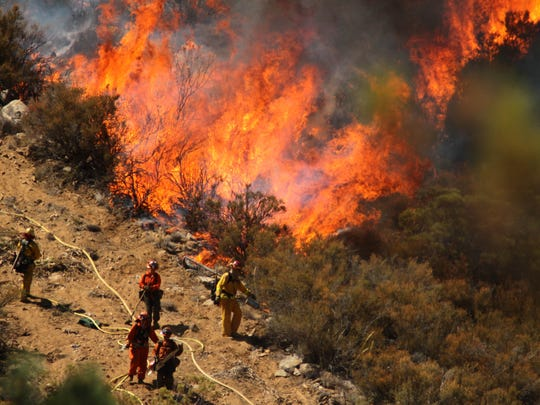 Firefighters attempt to stave off flames during the July 2013 Mountain Fire in the San Jacinto Mountains.