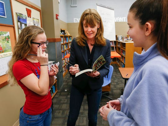 Children's author Kate Klise signs one of her books for Haylee Palmer, right, and Nauvianna Suntken after talking with their class about creative writing at Westport K-8 on Tuesday, March 28, 2017.