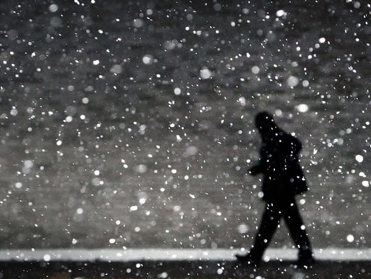 A traveler at the Memphis Airport hustles through falling snow to make his flight March 3, 2014, after a winter storm covered parts of Memphis in ice overnight.