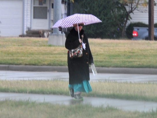 A pedestrian shields herself from rain Wednesday morning