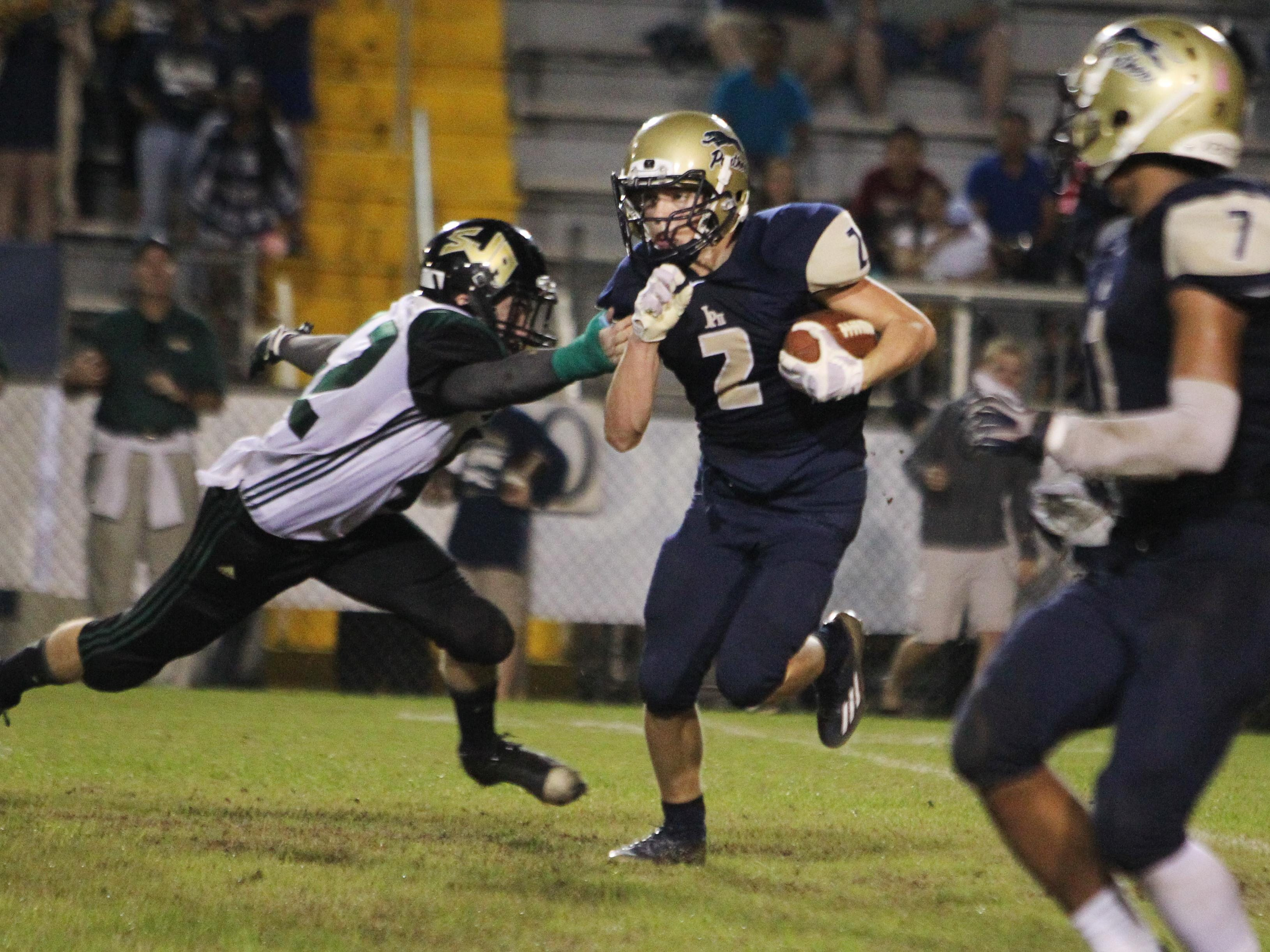 John Paul II's Taylor Janicki evades a defender on a punt return in the championship game of the North Florida Football Conference at Gene Cox Stadium.