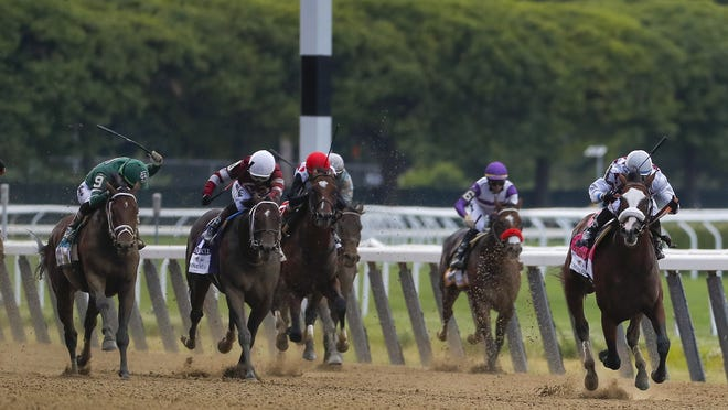 Tiz the Law, with jockey Manny Franco up, right, leads the pack down the home stretch during the 152nd running of the Belmont Stakes on Saturday.