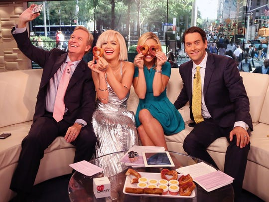 """Steve Doocy, Rita Ora, Elisabeth Hasselbeck and Clayton Morris have fun with heart-shaped cronuts from Dominique Ansel Bakery as she visits """"Fox & Friends"""" at the FOX Studios on Aug. 19, 2014, in New York City."""