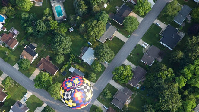 In this July 2015 photo, a Battle Creek neighborhood can be seen as a hot air balloon flies above the streets.