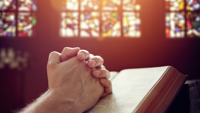 Hands folded in prayer on a Holy Bible.