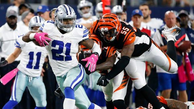 Dallas Cowboys running back Ezekiel Elliott (21) evades pressure from Cincinnati Bengals defenders Dre Kirkpatrick (27) and Vontaze Burfict (55) in the second half at AT&T Stadium.