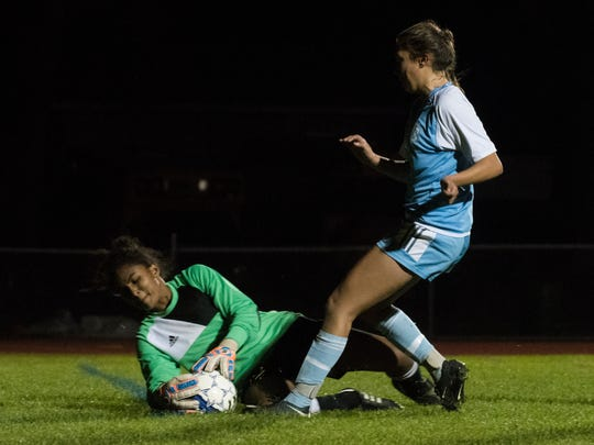 Essex goalie Yasmine Nsame makes a save from South Burlington's Olivia Dion (4) during the girls soccer game between the South Burlington Wolves and the Essex Hornets at Essex High School on Saturday night.