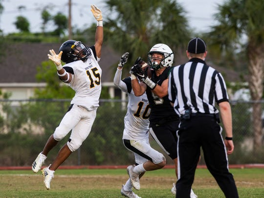 St. John Neumann running back Jensen Jones (5) catches the ball despite an attempted block by Bishop Verot defenseman Quan Chatman (15) during a spring football jamboree between the St. John Neumann, Bishop Verot and Island Coast teams at St. John Neumann High School in Naples on Wednesday, May 16, 2018.