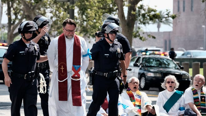 A clergy member is arrested during a civil disobedience protest in front of the federal courthouse in Los Angeles on Tuesday. Immigrant-rights advocates asked a federal judge to order the release of parents separated from their children at the border, as demonstrators decrying the Trump administration's immigration crackdown were arrested Tuesday at a rally ahead of a Los Angeles appearance by Attorney General Jeff Sessions.