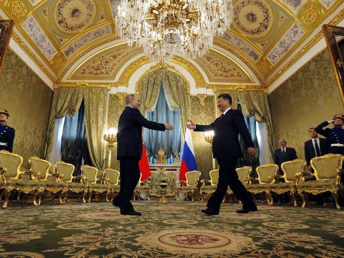 Russian President Vladimir Putin (L) welcomes Chinese
