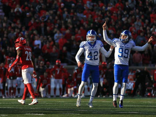 Kentucky kicker Austin MacGinnis celebrates with holder Tristan Yeomans after a 47-yard field goal from  with 12 seconds remaining for a 41-38 win.