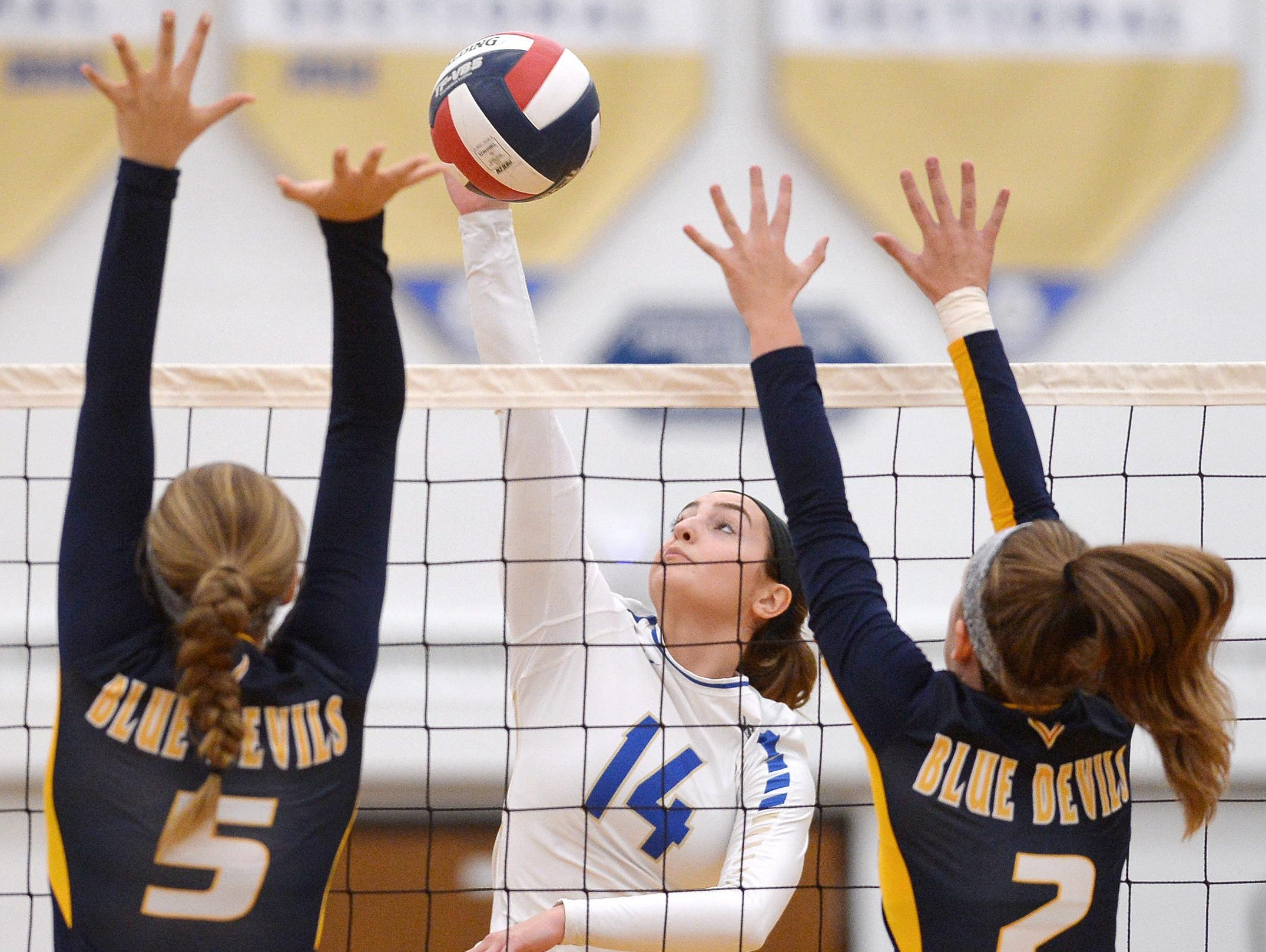 Webster Schroeder's Cristiana Tomassetti, center, hits between the block of Victor's Makenzie Bills (5) and Ally Devitte.