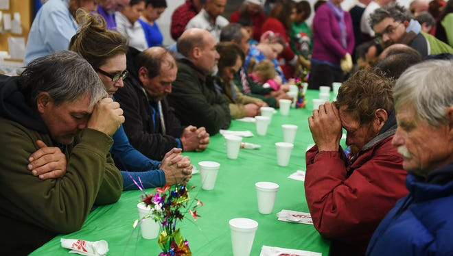 People pray before eating during a Christmas Day lunch for the homeless and needy in Reno, Nev.