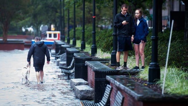 People hang out near the flooded walkway off River Street as a high tide and Tropical Storm Irma activity causes major flooding in Savannah, Ga. on Sept. 11, 2017.