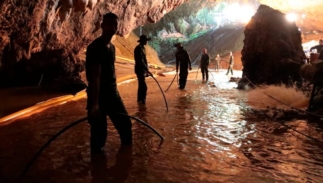 In this undated photo released by Royal Thai Navy, Thai rescue teams arrange water pumping system at the entrance to a flooded cave complex where 12 boys and their soccer coach have been trapped since June 23 in Mae Sai, Chiang Rai province.