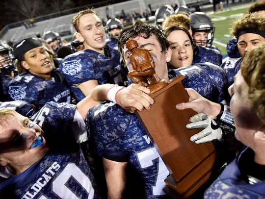 Dallastown's Raymond Christas kisses the Football for Freedom trophy after the Wildcats won a YAIAA football game Friday, Nov. 3, 2017, at Dallastown. Christas won the college scholarship awarded by the Quartback Club of York in February.