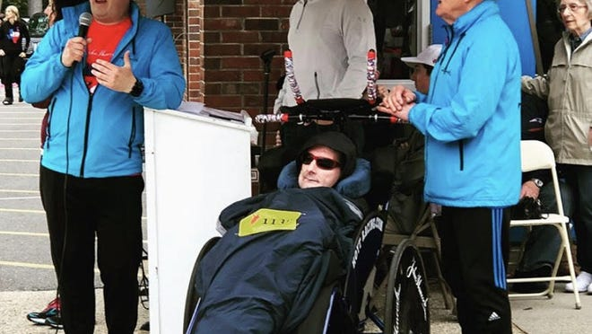 Billerica dentist and runner Bryan Lyons speaks to a crowd of fellow runners before the 2018 Holland 5K Road race. Next to him are prolific running duo Rick and Dick Hoyt. Bryan pushed the racechair of Rick Hoyt from 2015 until his sudden death in May.