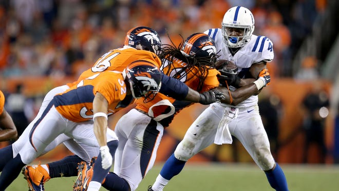 Indianapolis Colts Ahmad Bradshaw,right, bounces off of Denver Broncos Quinton Carter and other Broncos in the fourth. The Indianapolis Colts play the Denver Broncos Sunday, September 7, 2014, evening at Sports Authority Field at Mile High in Denver CO.
