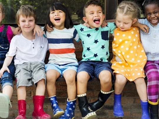 A row of children sitting on a bench and laughing