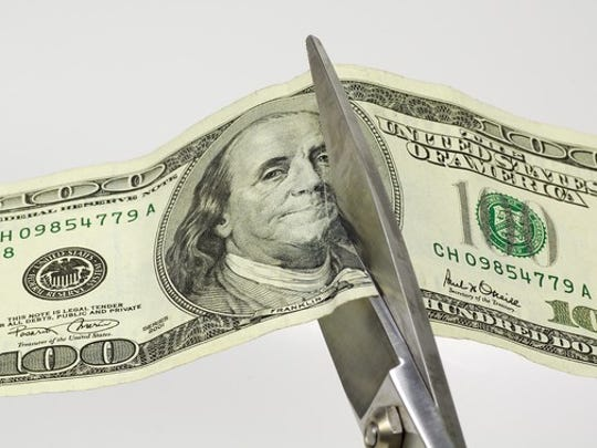 Scissors cutting through a hundred dollar bill.