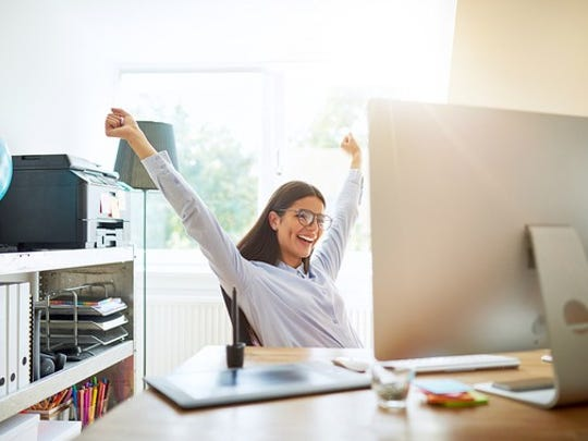 A smiling woman sitting at her desk in a home office.