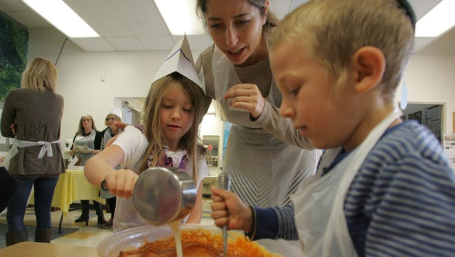 Sandy Birmingham supervises as Kristen Birmingham, 5, pours milk into the pumpkin pie mix, and Levi Lang, 5, stirs Sunday at Gan Camarillo Preschool in Camarillo. The pumpkin pies will be given to seniors through the Smile On Seniors program.
