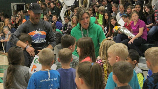 Cloudcroft elementary students give Matt and Cindy Preslar letters of support during a sendoff assembly. The couple are running in Monday's Boston Marathon.