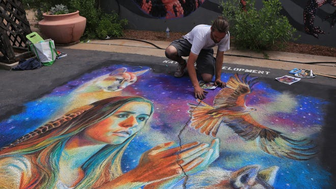 Rod Peterson finishes his piece Sunday afternoon at the Kayenta Street Painting Festival in Ivins City. Peterson won the award for Best Theme.