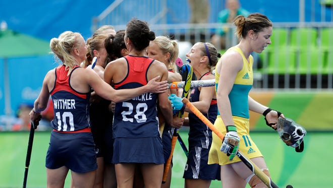 United States players, left, celebrate their first goal against Australia, as Australia's Karri McMahon, right, passes in front of them during a women's field hockey match at 2016 Summer Olympics in Rio de Janeiro, Brazil, Monday, Aug. 8, 2016.