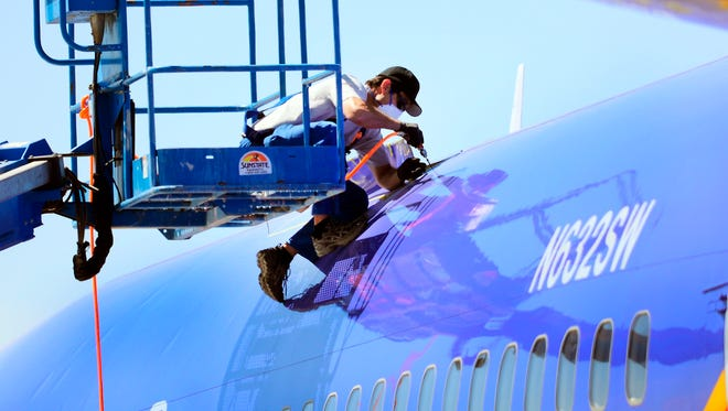 An investigator from the National Transportation and Safety Board cuts away a portion of the fuselage of Southwest Airlines Flight 812 two days after an emergency landing April 1, 2011, in Yuma, Ariz.