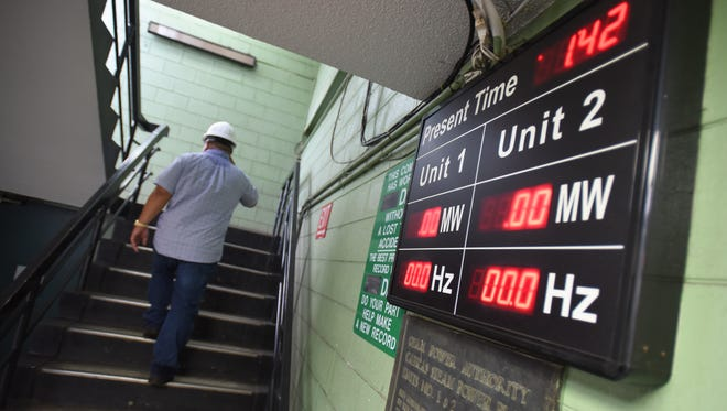 A display board shows no power output from Cabras Units 1 and 2 as Assistant Plant Superintendant Francis Cruz heads to the plant's second floor on Wednesday, Sept. 7.