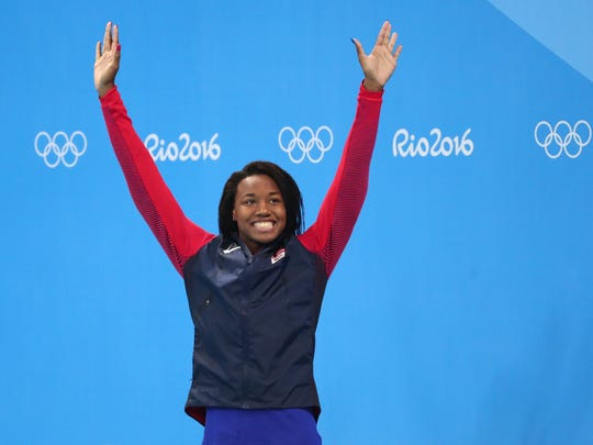 Stanford's Simone Manuel (USA) celebrates on the podium after the women's 50m freestyle final in the Rio 2016 Summer Olympic Games at Olympic Aquatics Stadium.