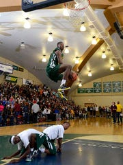 Teandre Jones jumps over two players Friday night during